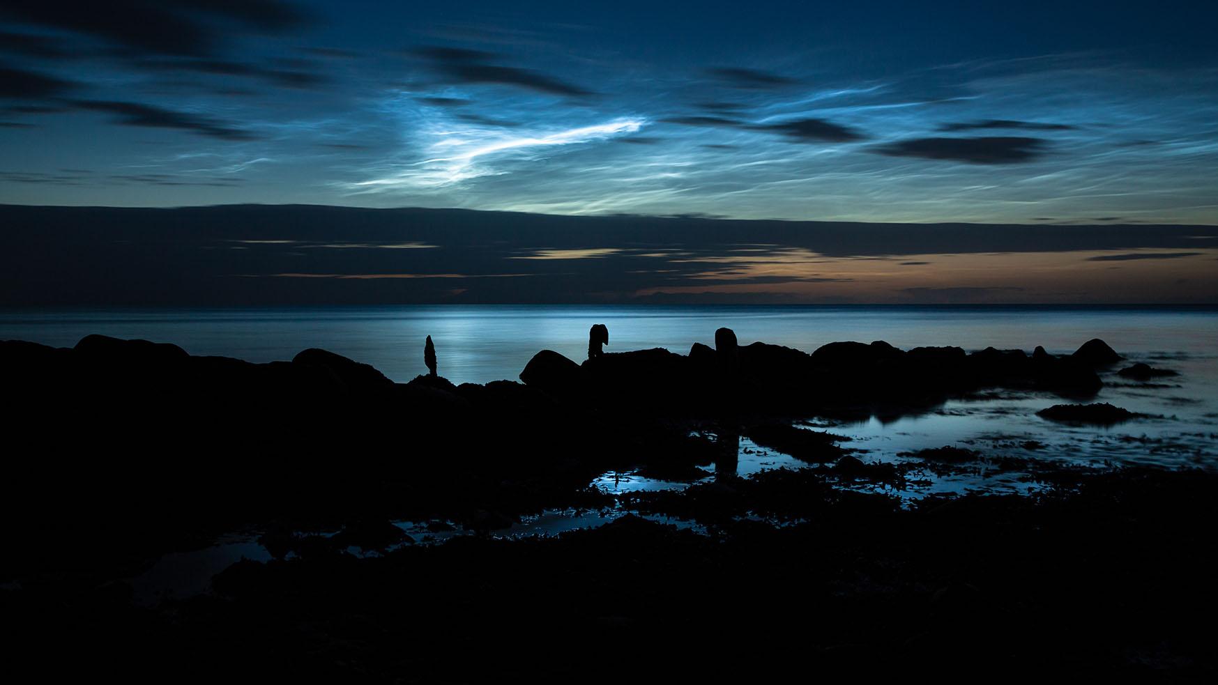 leuchtende Nachtwolken über einer Buhne in der Ostsee