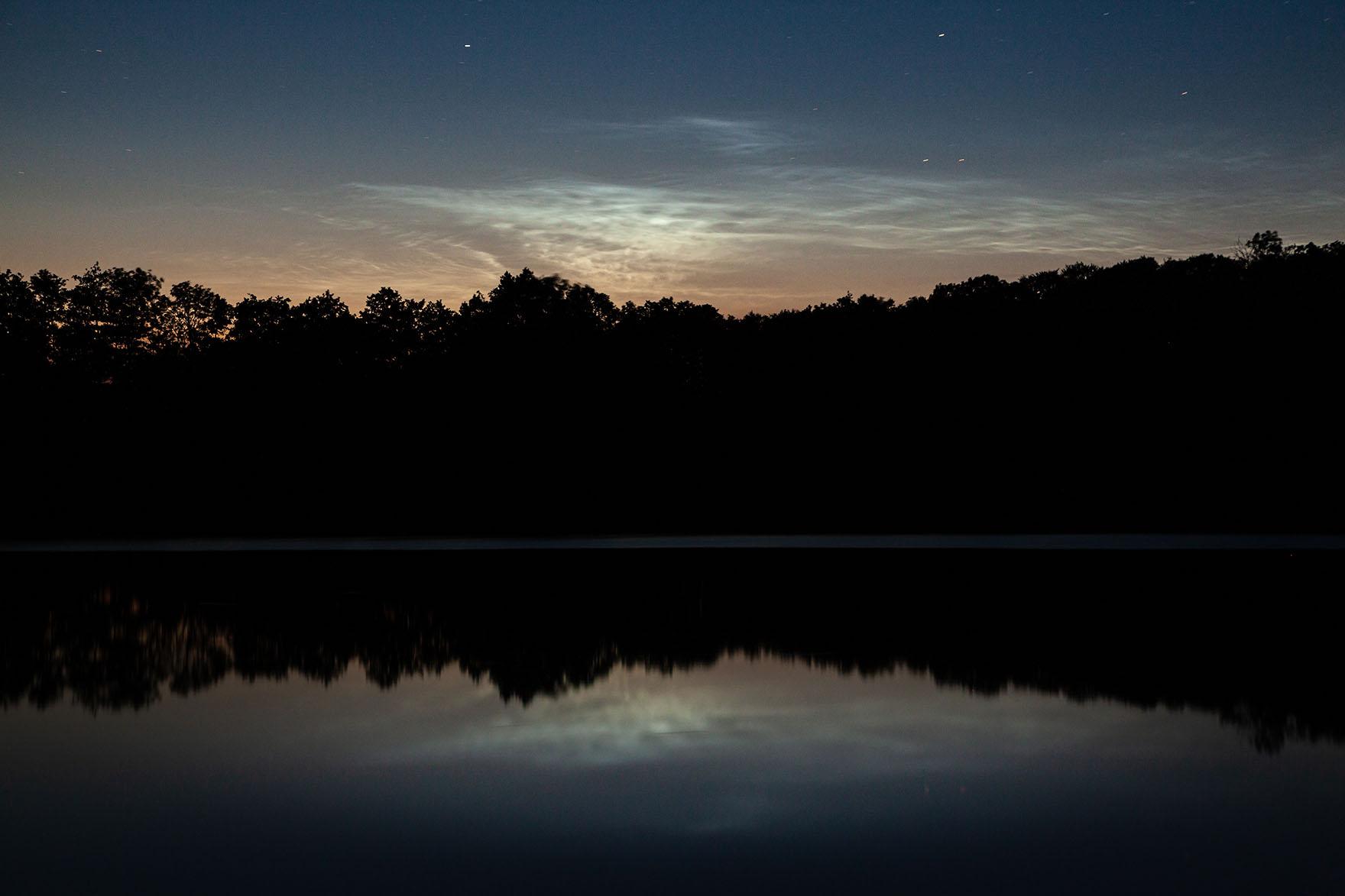 leuchtende Nachtwolken über einem kleinen See