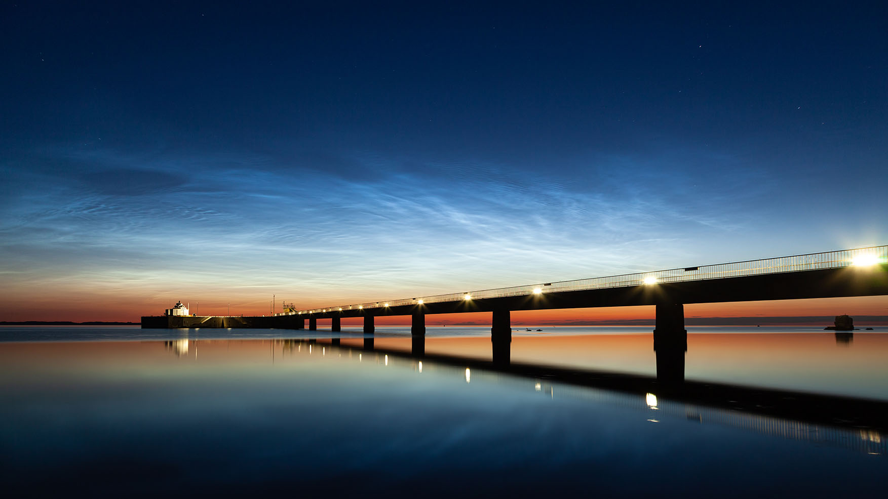 leuchtende Nachtwolken über einem Anleger in der Ostsee