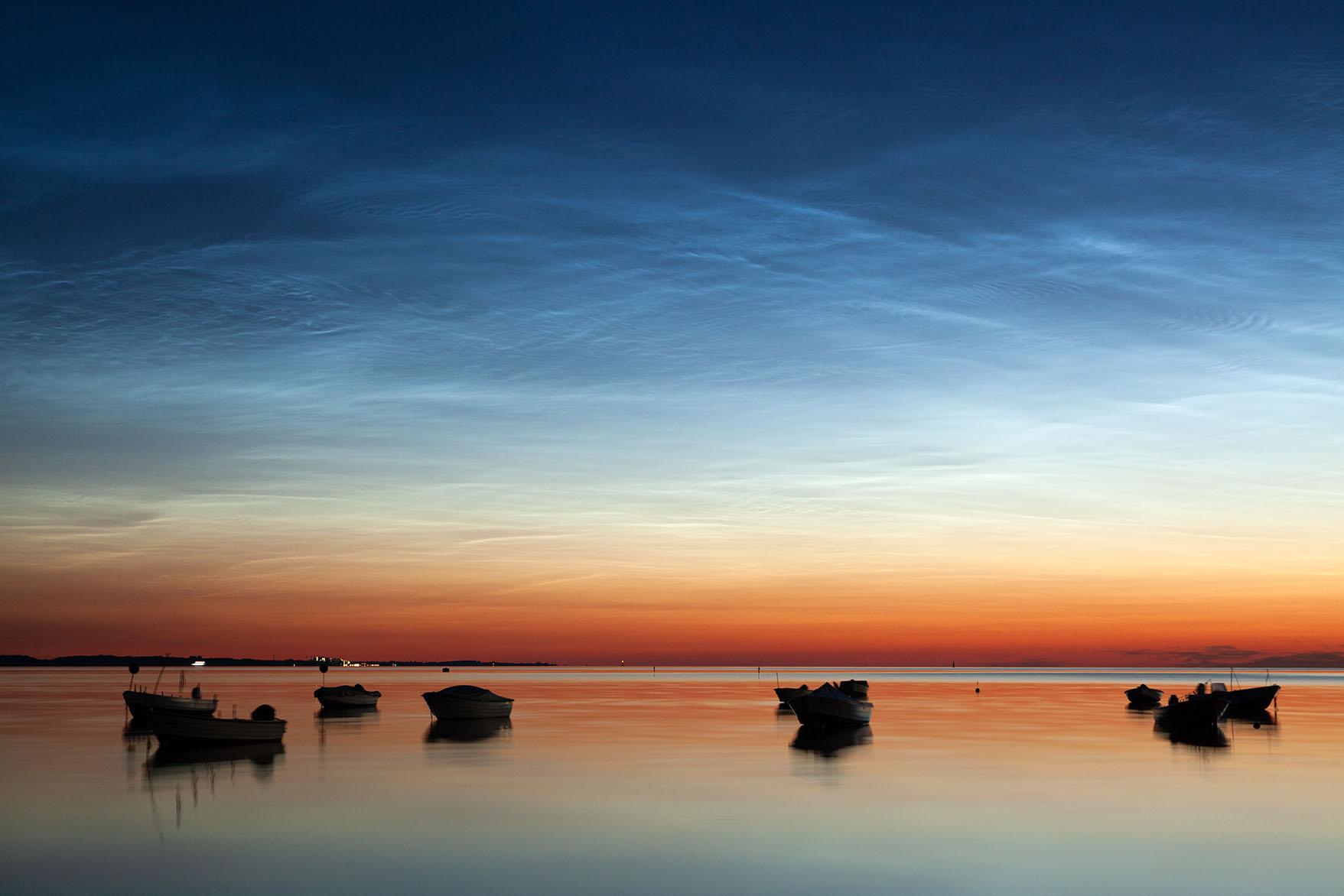 leuchtende Nachtwolken über Booten in der Ostsee