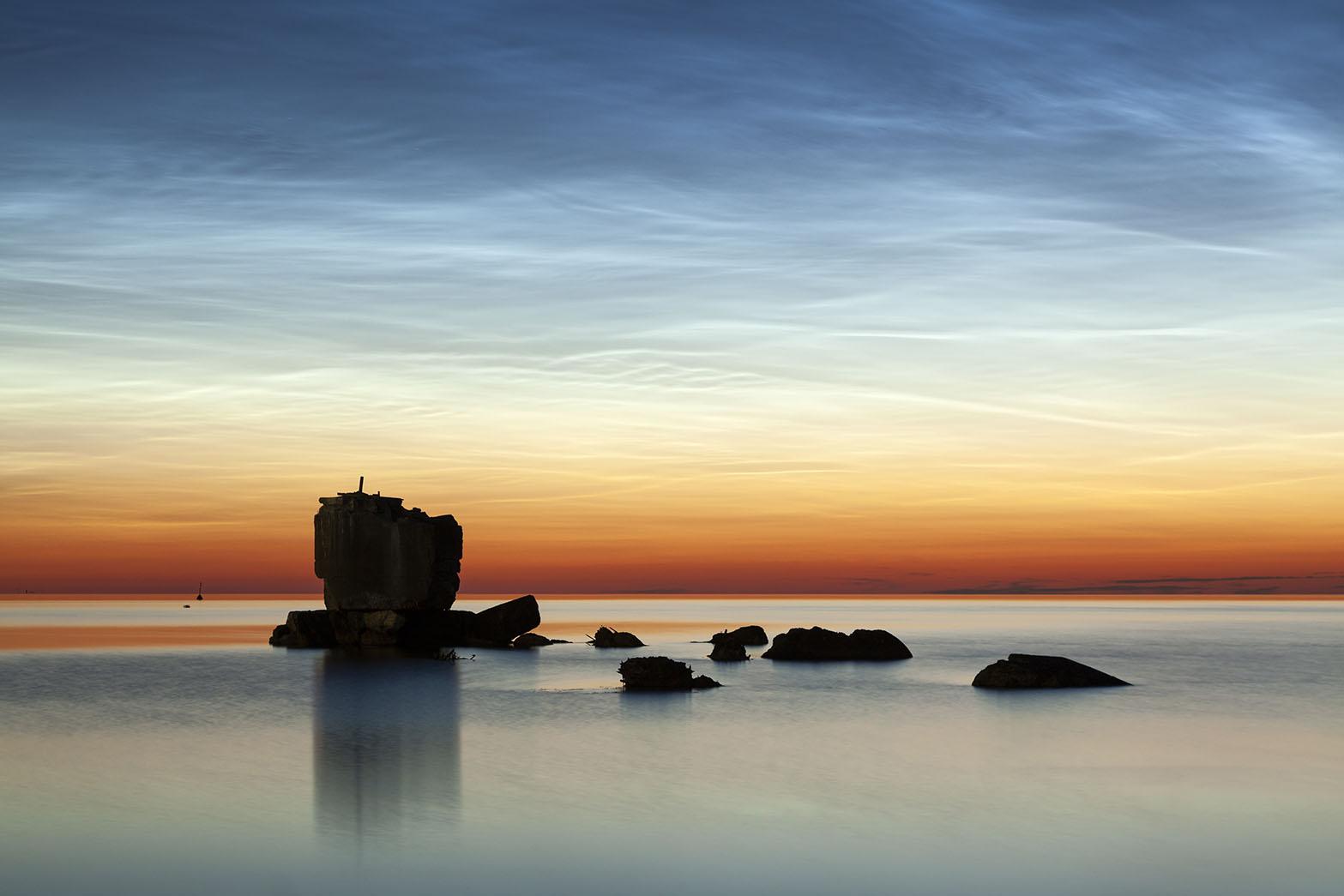 leuchtende Nachtwolken über einer Ruine in der Ostsee